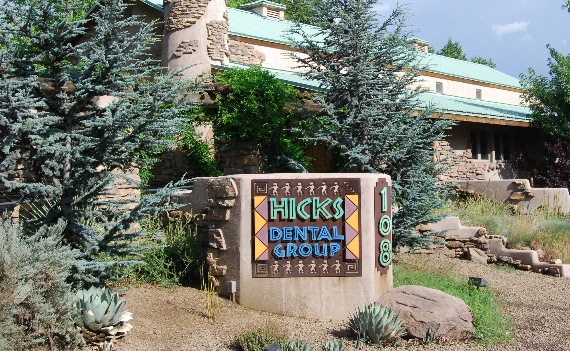 view of Hicks Dental Group building with surrounding plants and trees