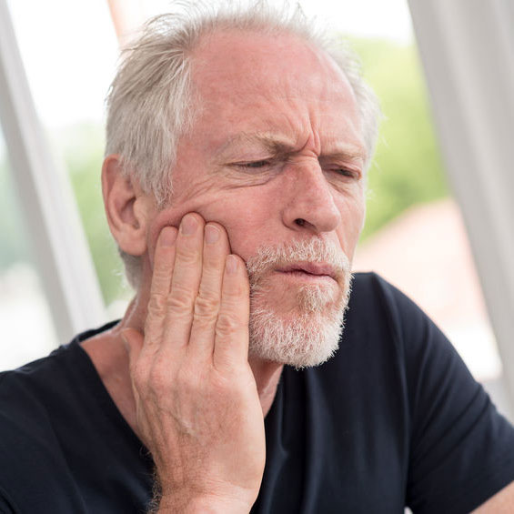 person holding jaw in pain