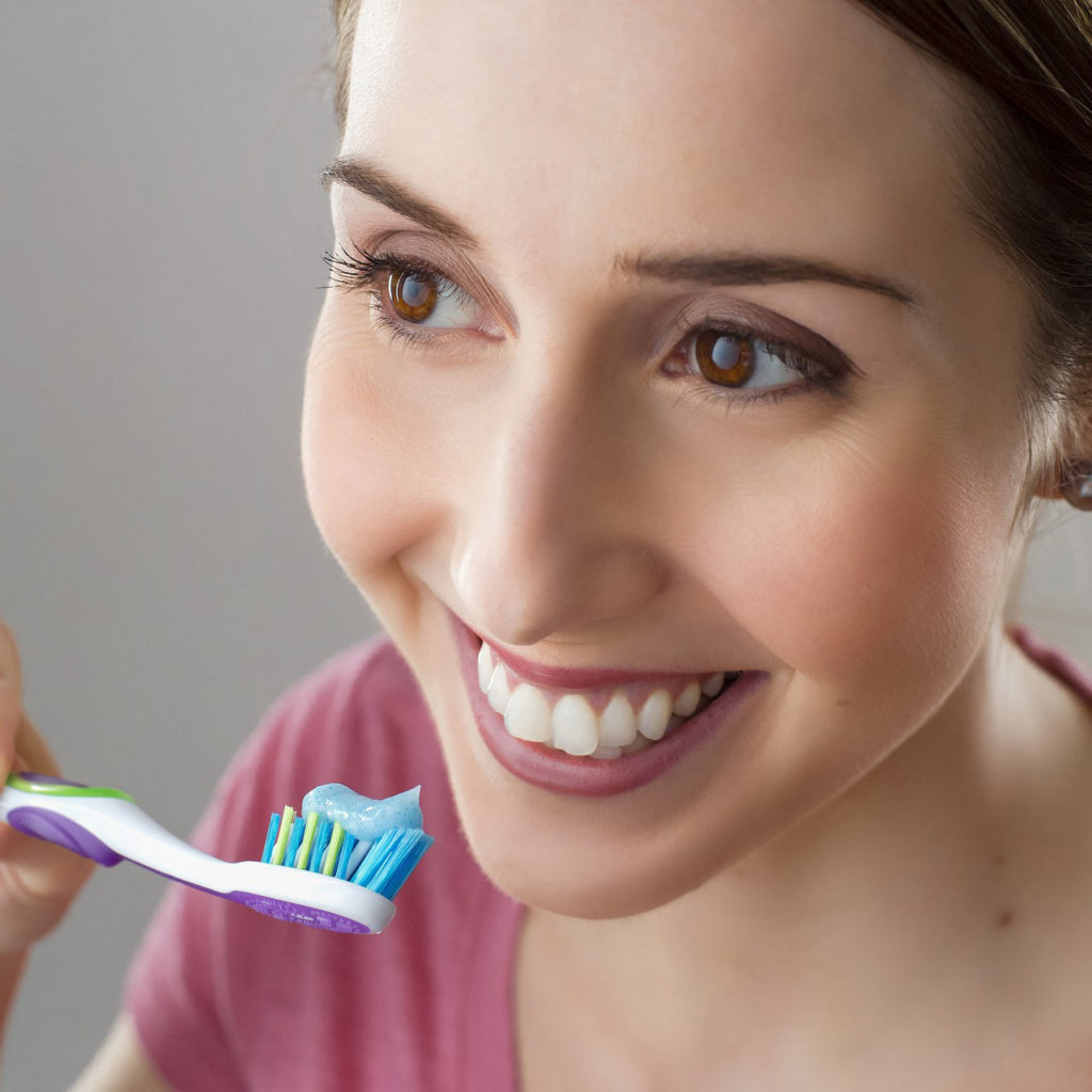 smiling person holding toothbrush near teeth