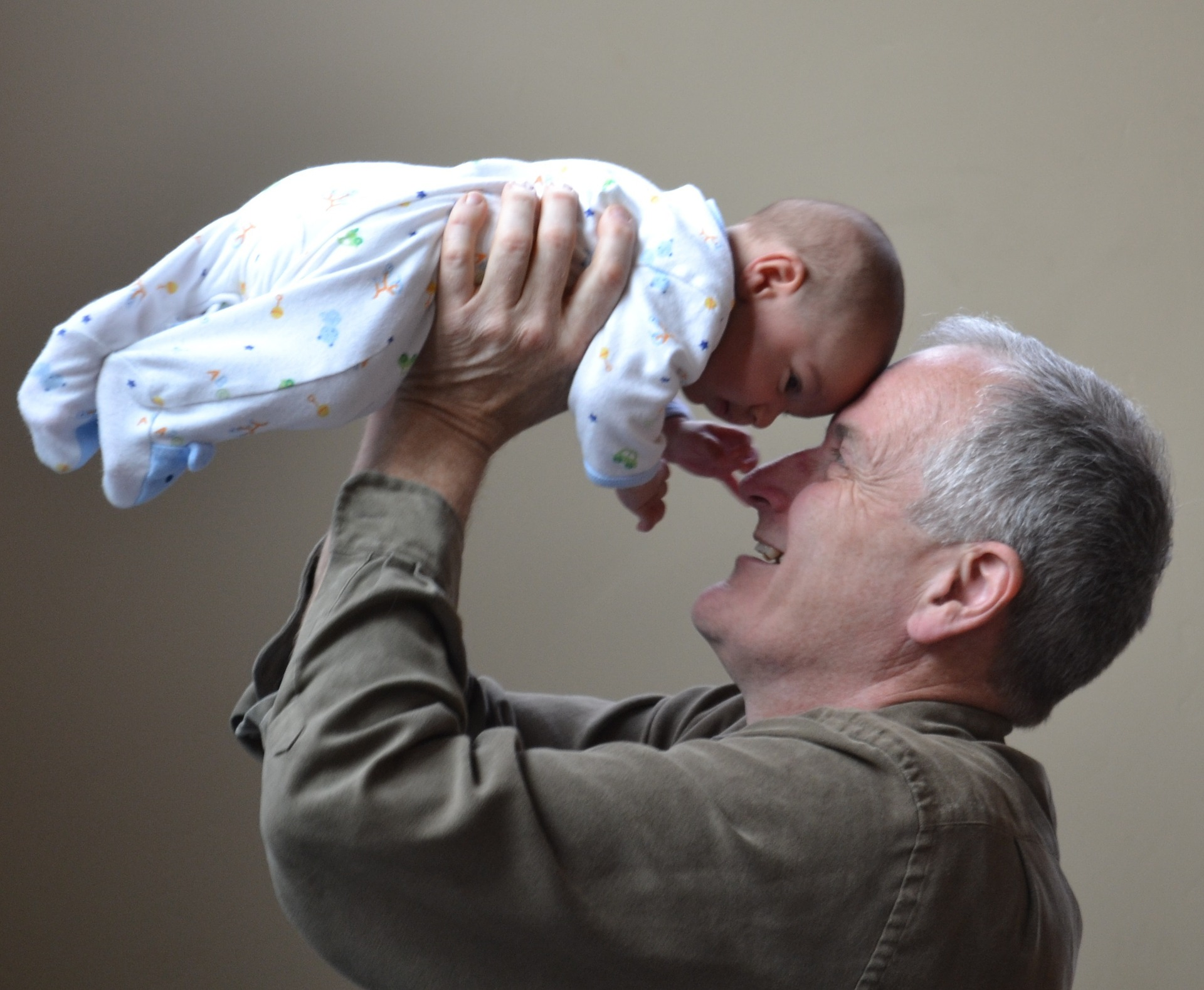 Aging and Dental Health in Prescott - grandfather holding up baby