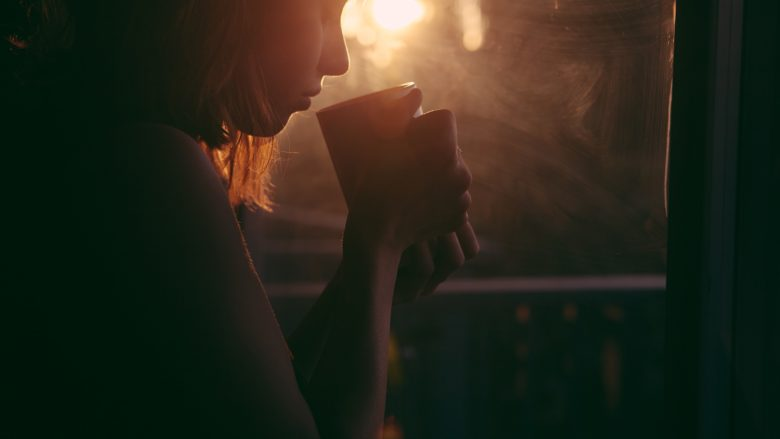 silhouette of person holding cup