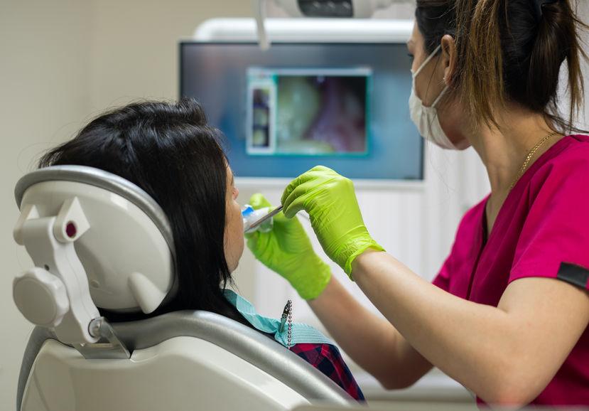 Dentist examining woman's teeth with camera