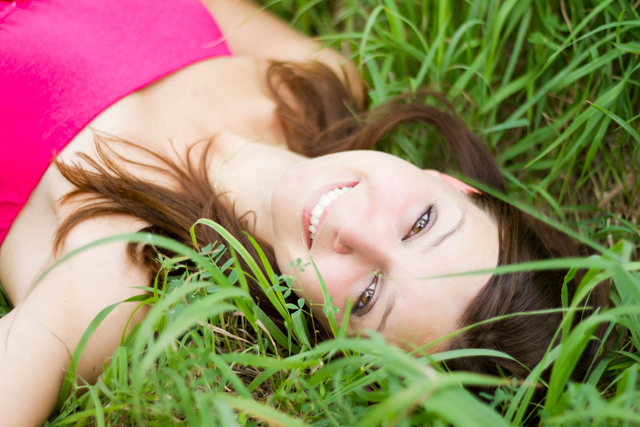 girl laying in grass smiling- what makes teeth yellow?