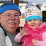 Grandpa smiling with granddaughter showing importance of senior dental care